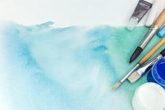 Pennelli e pitture dell'artista sopra le sedere verdi astratte dell'acquerello Fotografia Stock
