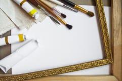 Pennelli e tela dell'artista sul fondo bianco della tela Principale v immagini stock
