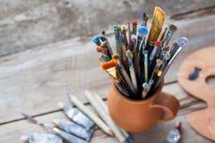 Pennelli in una brocca dai tubi dei vasai argilla, della tavolozza e della pittura Immagine Stock