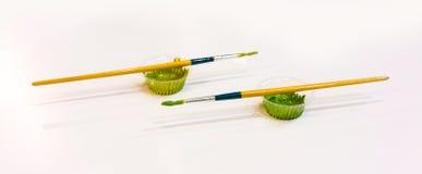 Pennelli variopinti con colore verde nel piccolo und di plastica della tazza Fotografie Stock