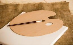 Pennello che si trova sul pallet di legno allo studio di arte Immagini Stock