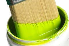 Pennello che si tuffa nella latta di vernice verde immagini stock