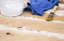 Pennello con una latta di pittura e dei guanti sui bordi di legno Preparazione per i bordi di verniciatura fotografia stock