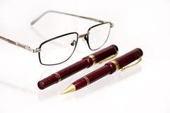 Pennen en glazen op een lijst. Stock Foto's