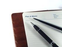 Pennen op een memorandumagenda Stock Afbeelding