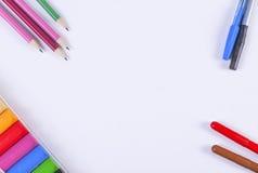 Pennen, potloden, kleurpotloden en klei die in de hoeken van een blad van document liggen Royalty-vrije Stock Foto