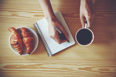 Pennhandstil på anteckningsboken med kaffe Arkivbild