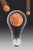 Pennies and light bulb. Copper US penny or one cent coin appearing to be inside a clear, incandescent light bulb Royalty Free Stock Image