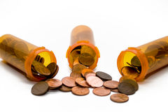 Pennies Rx. Three prescription medicine bottles with pennies. White background royalty free stock photography