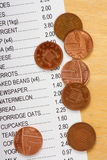 Pennies and Shopping List. Cost of living concept with a shopping list for groceries and foodstuffs and a few British pennies left over in change stock photography