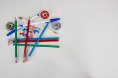 Pennor, blyertspennor, pushben och blyertspennashavings på vänstersida fotografering för bildbyråer