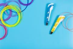 pennor 3d med den färgglade plast- glödtråden på blå bakgrund Royaltyfria Foton