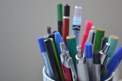 Pennor och blyertspennor i ställning Royaltyfri Bild
