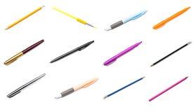 Pennor och blyertspennor på vit bakgrund arkivfoto