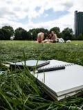 Pennpapper och ebookavläsare på gräset fotografering för bildbyråer