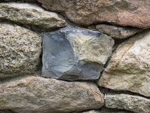 Pennsylvania Bluestone in a Farm Stone Wall. A rough fieldstone wall composed of a variety of Pennsylvania sandstone blocks with a piece of Bluestone in the Royalty Free Stock Photography