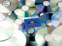 Pennsylvania flag on top of CD and DVD pile isolated on white. Pennsylvania flag on top of CD and DVD pile isolated Royalty Free Stock Photos