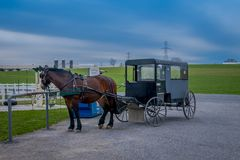 Pennsylvania, USA, APRIL, 18, 2018: Outdoor view of parked Amish buggy carriage in a farm with a horse used for a pull. The car in the streets in a gorgeous day Royalty Free Stock Image