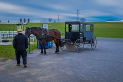 Pennsylvania, USA, APRIL, 18, 2018: Outdoor view of unidentified man walking close to a parked Amish buggy carriage in a. Farm with a horse used for a pull the Stock Photos