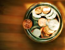 Penny. Balancing on a jar full of coins royalty free stock photography