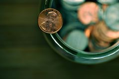 Penny. Balancing on a jar full of coins royalty free stock photo