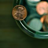 Penny. Balancing on a jar full of coins royalty free stock photos
