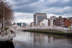 ` Penny Bridge för flod Liffey, mummeloch Heineken byggnad/O'Connell brohus i Dublin, Irland arkivbild
