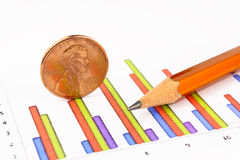 Penny coin with pencil standing on chart. Close-up Royalty Free Stock Photos