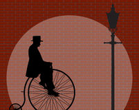 Penny Farthing Gentleman Brick Wall avec le projecteur Photo stock