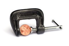 Penny pinching. Coin in a clamp representing the metaphor of penny pinching stock photos