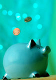 A penny saved. Blue piggy bank with pennies Royalty Free Stock Image