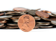 Penny saved is a penny earned. A penny standing in front of a pile of change Royalty Free Stock Photos