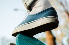Penny skateboard commute hipster transport solutions. Back view of the blue canvas skate shoe standing on the top of the blue plastic penny skateboard. Concept Royalty Free Stock Photo