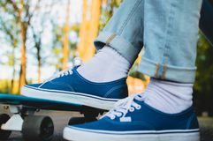 Penny skateboard commute hipster transport solutions. Close-up view of the feet weared in the blue canvas skate shoes standing at the blue plastic skateboard Stock Photo