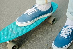 Penny skateboard commute hipster transport solutions. Side view of the blue canvas shoe standing on the blue plastic penny board outdoors. Concept of the modern Stock Photography