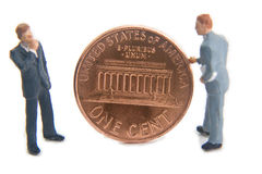 Penny for your thoughts. Miniature business men with an American penny Stock Photo