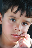 Penny for Your Thoughts. Thoughtful little boy with finger in the corner of his mouth and a penny in hand Royalty Free Stock Photos