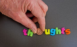 A penny for your thoughts!. An image of the word ' thoughts' in colorful lower case letters with the 'o' being replaced by a penny held in the fingers Stock Photo