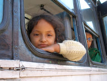 A penny for your thoughts, baby?. A girl peering out of the bus window, India Stock Photography