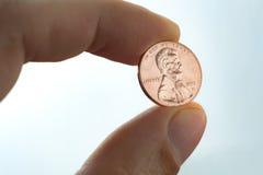 Pennynahaufnahme, Münze in der Hand, US-Münze auf Finger neigt sich Lizenzfreie Stockfotos
