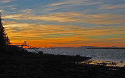 Penobscot Bay Maine Sunset. Colorful sunset over Penobscot Bay, Maine from Deer Isle Maine with dock and shore in forefront and Camden Hills in the distance Stock Image