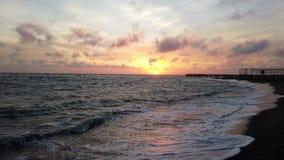 Penombra di stupore al tramonto sulla spiaggia nella costa romana del lido di Ostia, con le onde che si rompono sulla riva video d archivio
