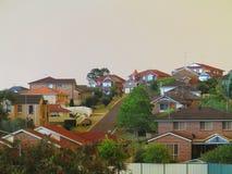 Penombra sopra le case moderne dagli incendi di arbusti Immagini Stock