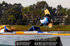 Wakeboarder in mid-air. PENRITH,AUSTRALIA - JUNE 26,2016: A wakeboarder somersaults off a ramp at Cables Wake Park. An electrical cable system pulls people royalty free stock photo