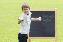 Pensée, écriture et comptant de garçon sur le tableau noir Fond extérieur vert Image stock