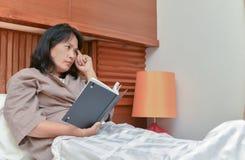 Pensée d'épouse et livre lu dans la chambre à coucher Images libres de droits