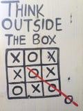Pensée en dehors de la boîte dans un tableau noir blanc Photographie stock