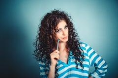 Pensée femme avec le stylo de participation de pensée de cheveux bouclés sur la joue vous regardant avec scepticisme images libres de droits