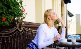 Pensées agréables Appréciez sa vie Le visage de sourire rêveur blond de femme ont plaisir à avoir le café, fond urbain defocused images libres de droits