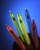 Pens. Group of colored pens isolated on a blue background royalty free stock photos
